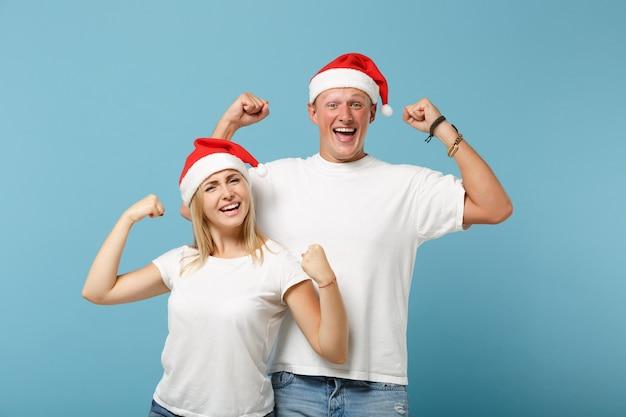 Fröhliche junge santa paar freunde kerl und frau in weihnachtsmütze posiert