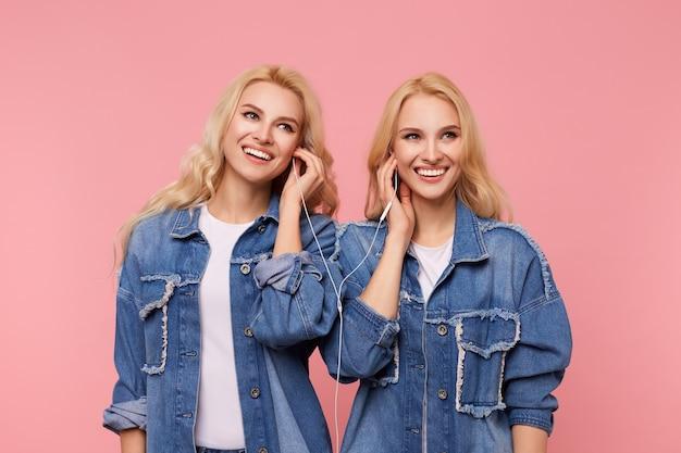 Fröhliche junge schöne blonde damen mit gewellten frisuren, die glücklich lächeln, während sie musik in den kopfhörern genießen, während sie über rosa hintergrund stehen