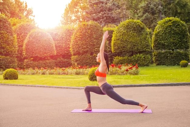 Fröhliche junge schöne frau, die yoga im park praktiziert und aufwirft.