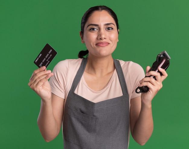 Fröhliche junge schöne frau friseur in der schürze hält trimmer und kreditkarte, die vorne mit lächeln auf gesicht steht, das über grüner wand steht