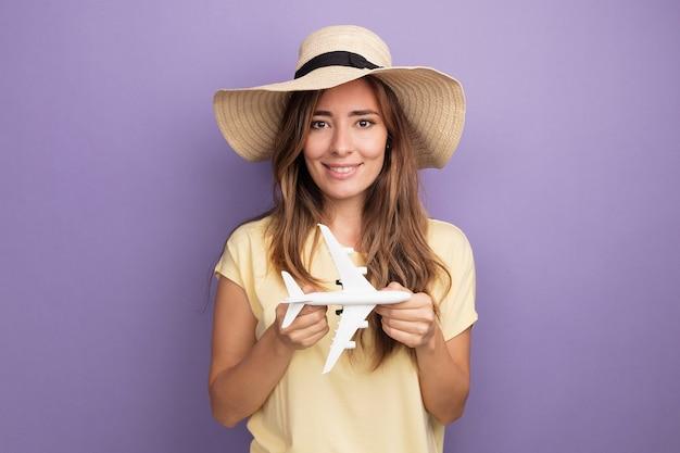 Fröhliche junge schöne frau in beigefarbenem t-shirt und sommerhut, die ein spielzeugflugzeug hält und die kamera mit einem lächeln auf dem gesicht auf violettem hintergrund anschaut