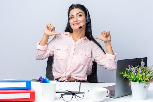 Fröhliche junge schöne frau in freizeitkleidung mit kopfhörern und mikrofon lächelt selbstbewusst und zeigt auf sich selbst am tisch sitzend mit laptop über weißer wand, die im büro arbeitet