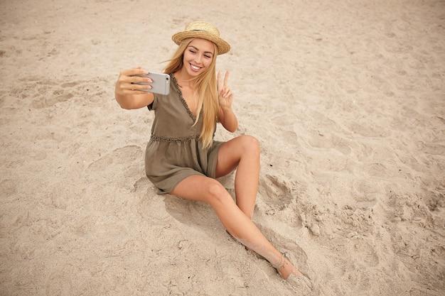 Fröhliche junge schöne langhaarige blonde dame im bootshut, die glücklich an der kamera ihres handys lächelt, während sie ein foto von sich selbst macht und auf sand über strandküste sitzt