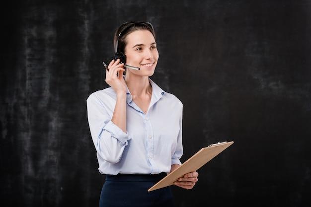 Fröhliche junge sekretärin oder betreiberin mit zwischenablage, die mit kunden im mikrofon über schwarzem hintergrund spricht