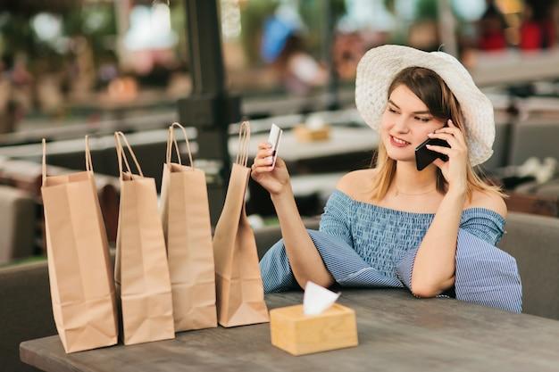 Fröhliche junge shopaholic frau, die im straßencafé sitzt, während sie am telefon spricht und bankkarte in ihrer hand hält