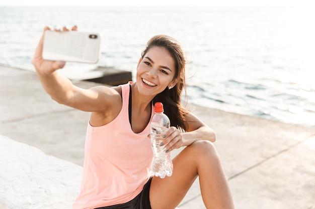 Fröhliche junge sportlerin, die sich nach dem training am strand ausruht, ein selfie macht und wasser trinkt