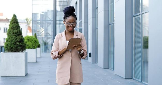 Fröhliche junge stilvolle geschäftsfrau des afroamerikaners in den gläsern, die draußen gehen und tablet-gerät verwenden. schöne lächelnde frau, die auf gadget-computer tippt und scrollt, während sie auf der straße spaziert.