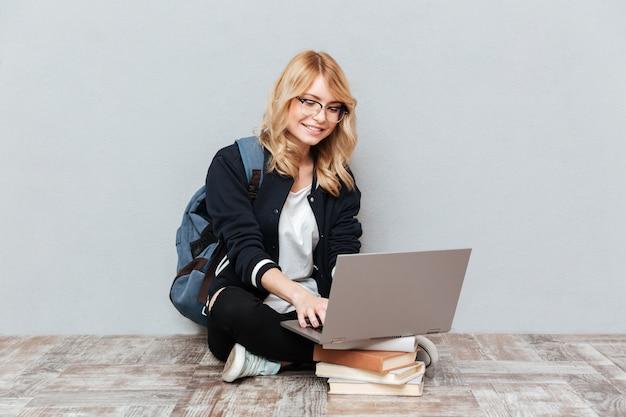 Fröhliche junge studentin mit laptop-computer.