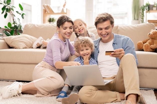 Fröhliche junge vierköpfige familie, die auf dem boden des wohnzimmers sitzt und im online-shop surft