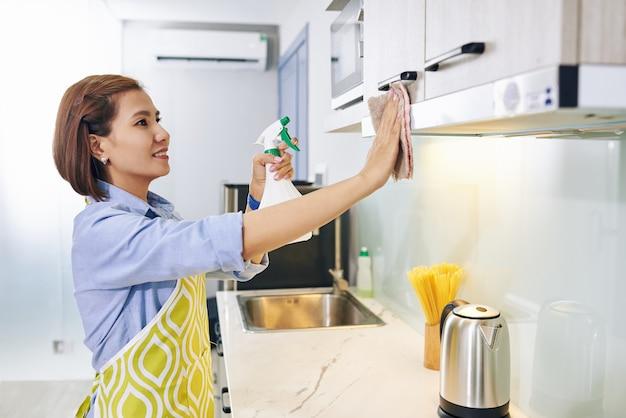 Fröhliche junge vietnamesische hausfrau, die küchenschränke mit desinfizierendem spray reinigt