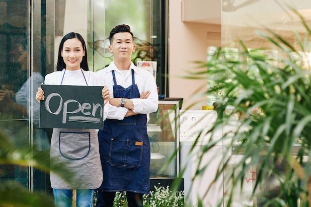 Fröhliche junge vietnamesische kellner eröffnen das café, nachdem sie kunden unter quarantäne gestellt und eingeladen haben