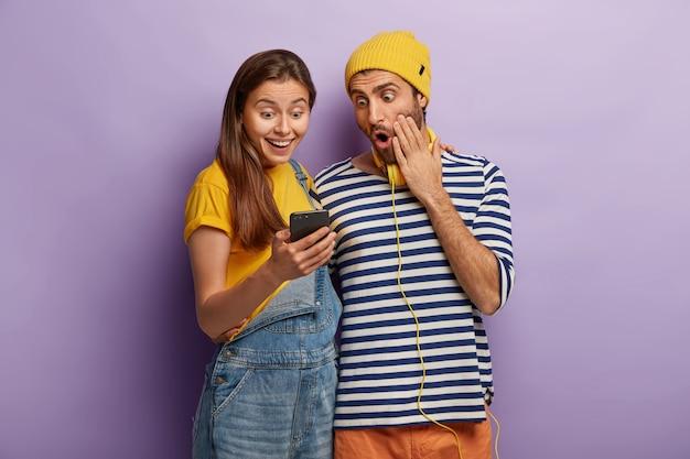 Fröhliche junge weibliche und männliche benutzer moderner technologien fühlen sich durch erfolgreiche smartphoe-aktualisierungen wohl, sehen überraschend auf das display, tragen modische kleidung, schauen sich videos online an und installieren die app