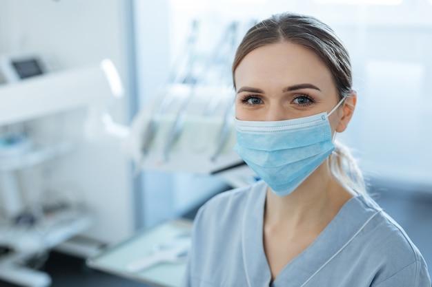 Fröhliche junge zahnärztin, die in ihrem büro aufwirft und lächelt, während sie eine gesichtsmaske trägt