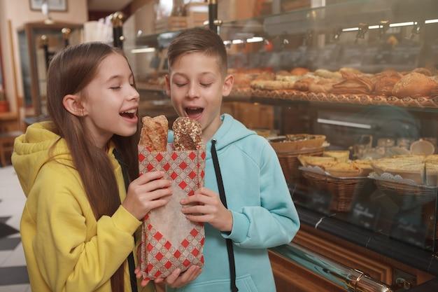 Fröhliche junge zwillinge beißen köstliches frisch gebackenes brot in der bäckerei