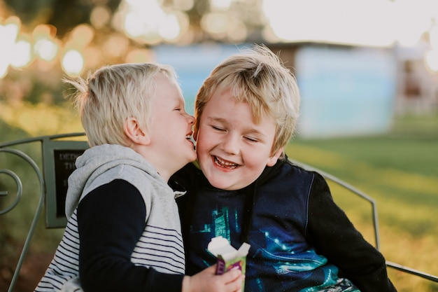 Fröhliche jungs aus australien sitzen auf einer bank und haben spaß