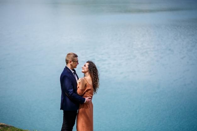 Fröhliche jungvermählten halten händchen und lachen vor dem hintergrund eines sees und einer grünen wiese. fröhlicher bräutigam und schöne braut mit lockigem haar gehen auf der wiese