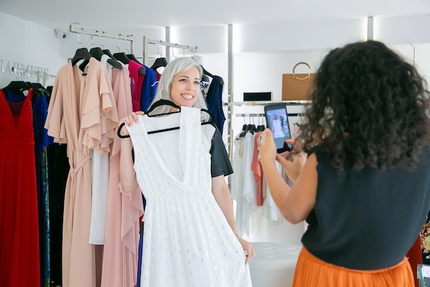 Fröhliche käuferinnen genießen das gemeinsame einkaufen im kleidergeschäft, halten das kleid, posieren und fotografieren auf dem handy. konsum- oder einkaufskonzept