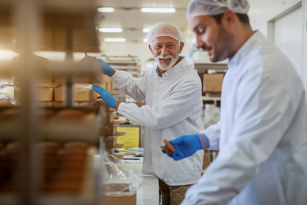 Fröhliche kaukasische angestellte in weißen sterilen uniformen, die kekse in kisten verpacken, während sie in der nahrungspflanze stehen.