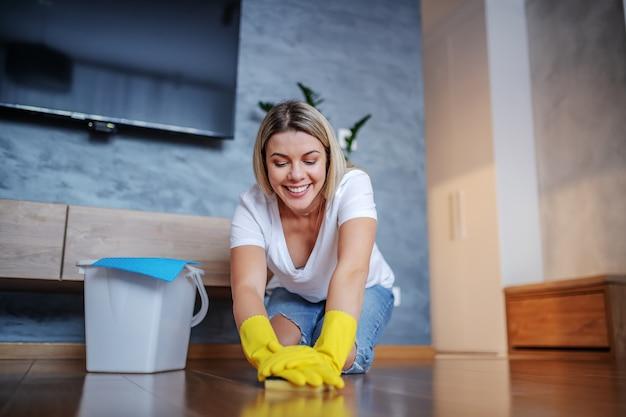 Fröhliche kaukasische blonde junge hausfrau gekleidet lässig kniend auf dem boden im wohnzimmer und wischen boden mit schwamm. neben ihr steht ein eimer mit waschmittel. hausarbeit.