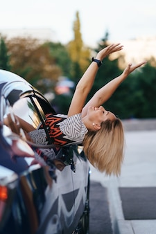 Fröhliche kaukasische frau fährt durch die malerische sonnige stadt und winkt mit den armen, während sie sich an einem schönen tag aus dem autofenster streckt