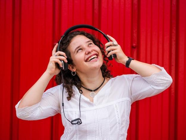 Fröhliche kaukasische frau hört musik mit kopfhörern auf roter szene