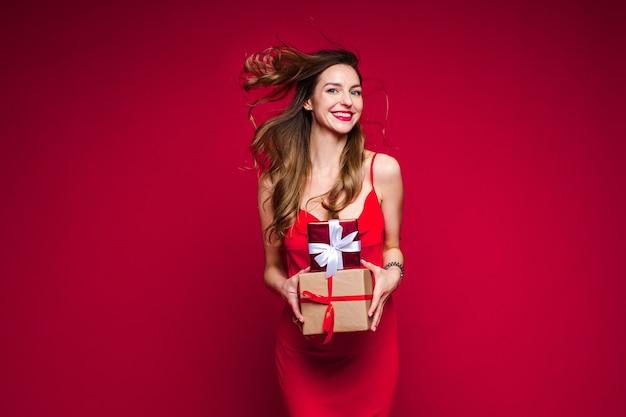 Fröhliche kaukasische frau mit attraktivem aussehen mit vielen feiertagsgeschenken, bild lokalisiert auf roter wand