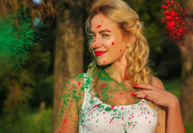 Fröhliche kaukasische frau mit langem, gewelltem haar, die mit farbspritzer einer trockenen holi-farbe posiert