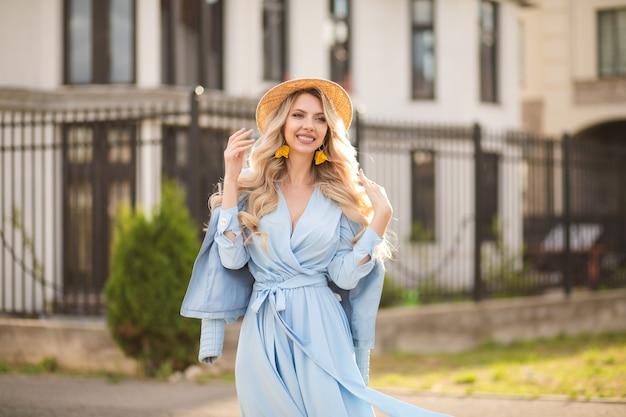 Fröhliche kaukasische frau mit langen blonden haaren, blauen augen und perfektem lächeln im langen blauen kleid mit hut geht draußen in der nähe der gebäude