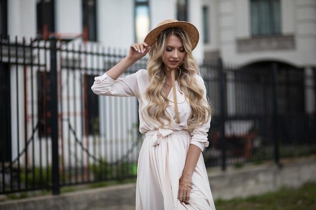Fröhliche kaukasische frau mit langen blonden haaren, blauen augen und perfektem lächeln im langen weißen kleid mit hut geht draußen in der nähe der gebäude