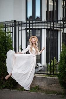 Fröhliche kaukasische frau mit langen blonden haaren, blauen augen und perfektem lächeln im langen weißen kleid mit hut geht draußen in der nähe der häuser