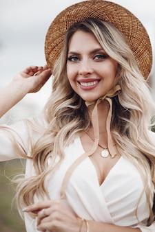 Fröhliche kaukasische frau mit langen blonden haaren, blauen augen und perfektem lächeln im langen weißen kleid mit hut geht nach draußen