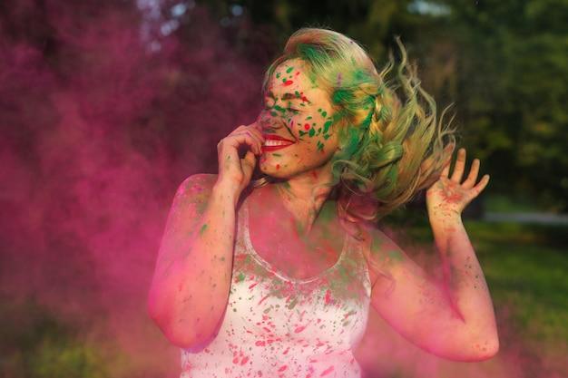 Fröhliche kaukasische frau mit lockigem haar, die eine wolke aus rosafarbener trockener farbe steht und das holi-festival feiert