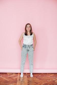 Fröhliche kaukasische frau mit mittlerem haar in weißem t-shite, blue jeans lächelt