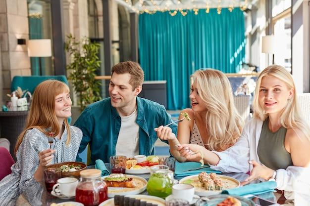 Fröhliche kaukasische freunde, die zeit zusammen im hellen gemütlichen zeitcafé verbringen