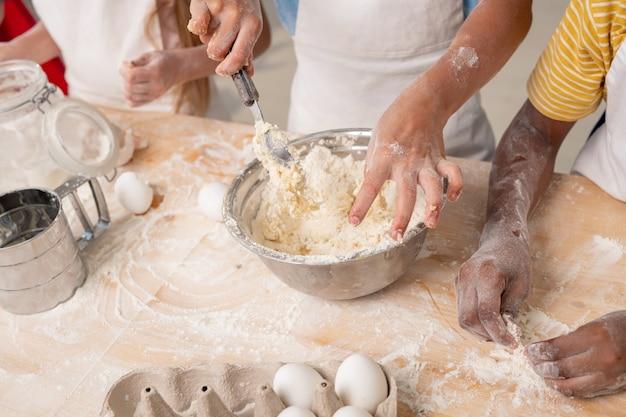 Fröhliche kinder, die in einer geräumigen küche stehen und ihnen beibringen, wie man gemüsesalat kocht, gruppenporträt