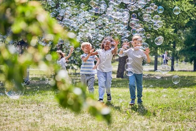 Fröhliche kinder, die mit seifenblasen spielen