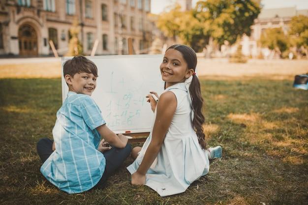 Fröhliche kinder, die zahlen auf whiteboard in der natur schreiben