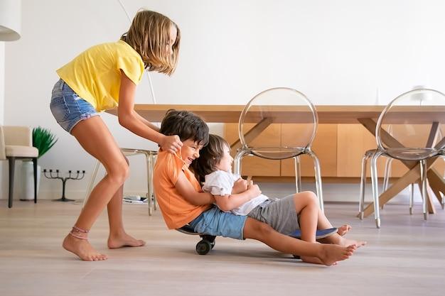 Fröhliche kinder, die zu hause mit skateboard spielen. blondes entzückendes mädchen, das ihre zwei verspielten brüder schiebt. glückliche kinder, die an bord reiten und spaß haben. kindheit, spielaktivität und wochenendkonzept