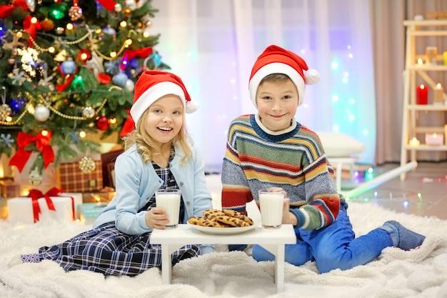 Fröhliche kinder essen im geschmückten weihnachtszimmer