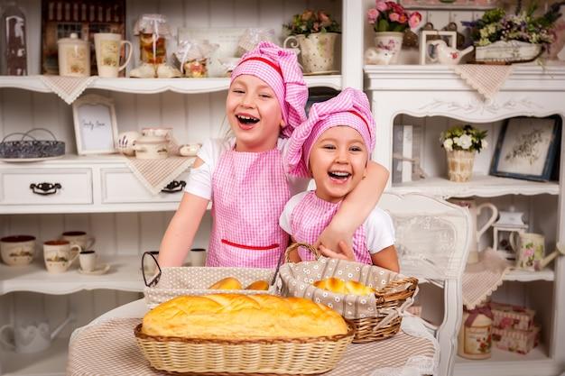 Fröhliche kinder lachen in der küche am tisch beim backen