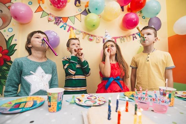 Fröhliche kinder mit partyhörnern