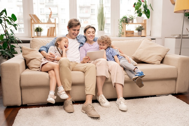Fröhliche kinder und ihre eltern in freizeitkleidung entspannen auf der couch im wohnzimmer