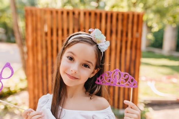 Fröhliche kleine dame mit großen braunen augen, die rosa spielzeugkrone halten und mit vergnügen im hof posieren. nahaufnahmeporträt im freien des lächelnden brünetten mädchens mit funkelnden gläsern in der hand.