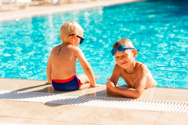 Fröhliche kleine kinder haben spaß am pool des ferienortes