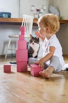 Fröhliche kleinkinderanordnung rosa würfel, die turmlehrmaterialien für maria montessori zusammenbauen
