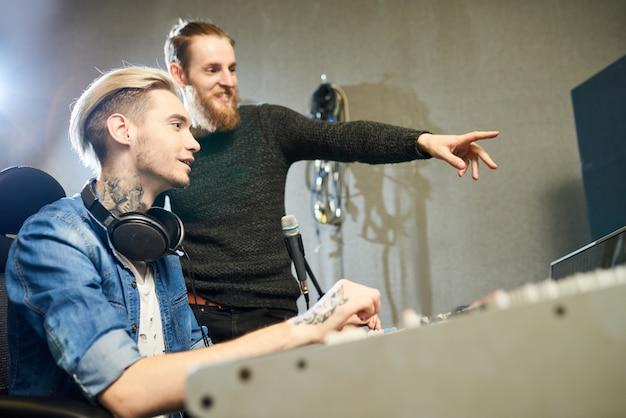 Fröhliche kollegen, die im studio musik machen