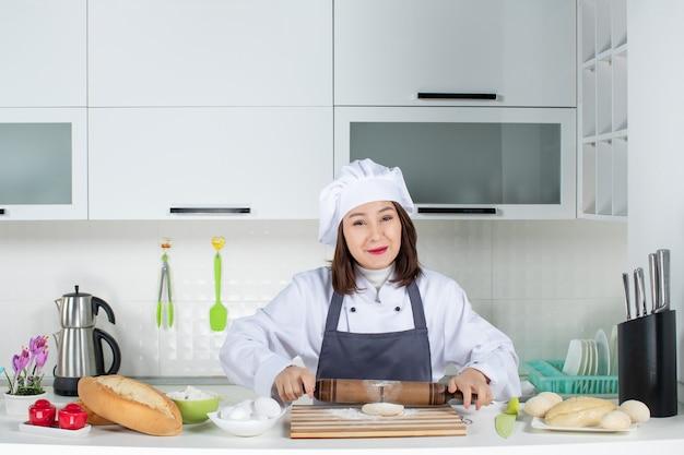 Fröhliche kommischefin in uniform, die hinter dem tisch steht und gebäck in der weißen küche zubereitet