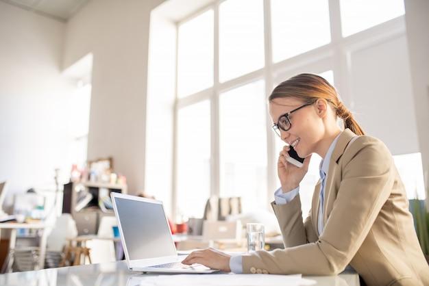 Fröhliche kommunikative junge geschäftsfrau mit pferdeschwanz, der am schreibtisch sitzt und laptop verwendet, während auf handy spricht und mit kunden arbeitet