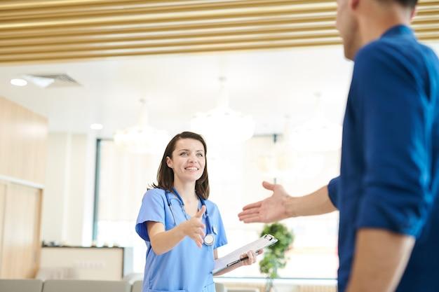 Fröhliche krankenschwester grußpatient