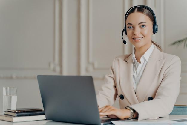 Fröhliche kundenbetreuerin, die am computer im modernen callcenter-büro arbeitet, glückliche geschäftsfrau, die in die kamera lächelt, während sie an ihrem arbeitsplatz mit computer sitzt